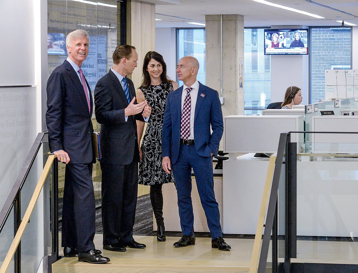 Touring the Post with MacKenzie and publisher Fred Ryan (far left). When Post execs have visited the Bezos estate outside Seattle, Bezos has made breakfast. Photograph by Bill O'Leary/Washington Post via Getty Images.
