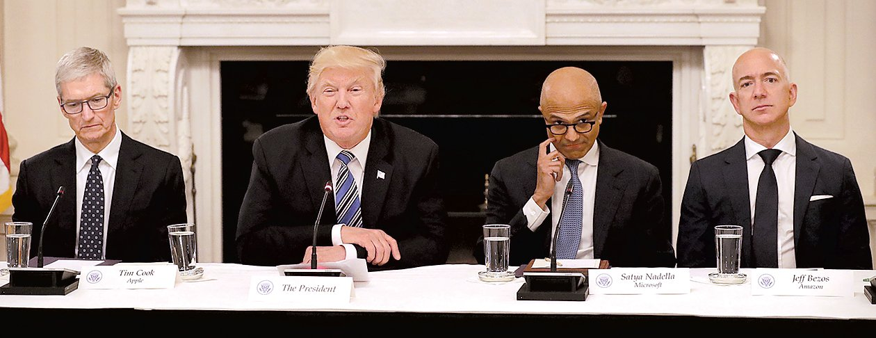 "At the White House for a meeting of tech leaders in June 2017, by which point Trump was fond of attacking Bezos's ""Amazon Washington Post"" on Twitter. Photograph by Chip Somodevilla/Getty Images."