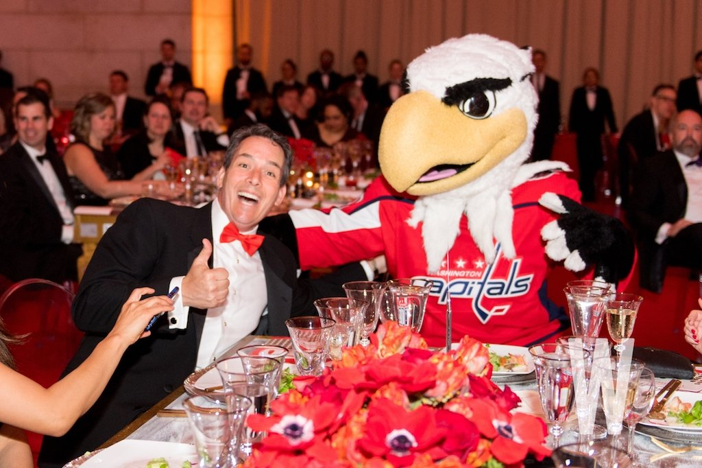 A guest mugs with the Washington Capitals' Slapshot mascot.