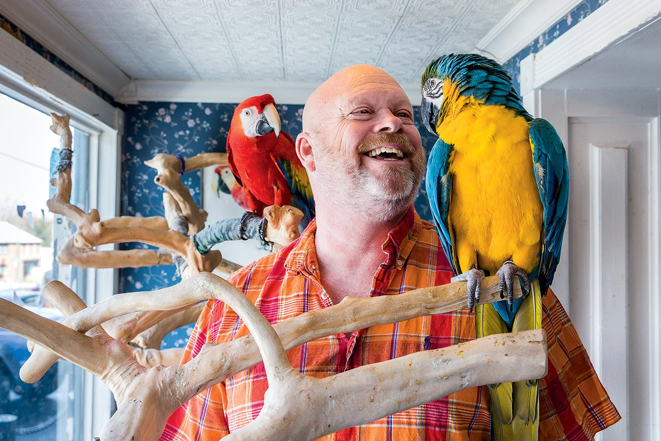 Store owner Ed Willis with two macaws. Photograph by April Greer.