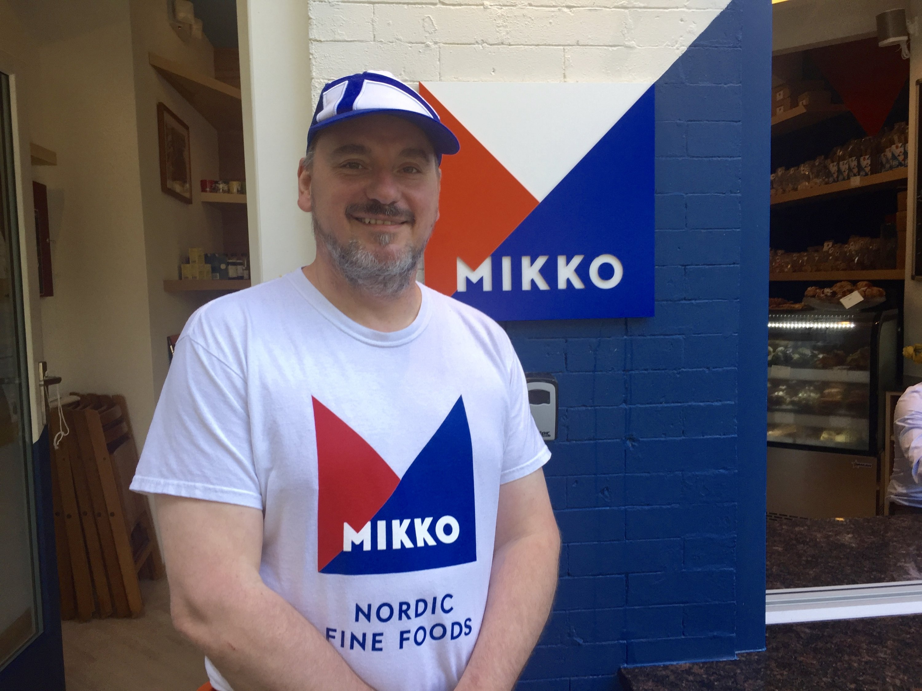 Chef Mikko Kosonen (who is wearing a hat in the pattern of the flag of Finland) stands in front of his new restaurant, Mikko. Photograph by Helen Carefoot.
