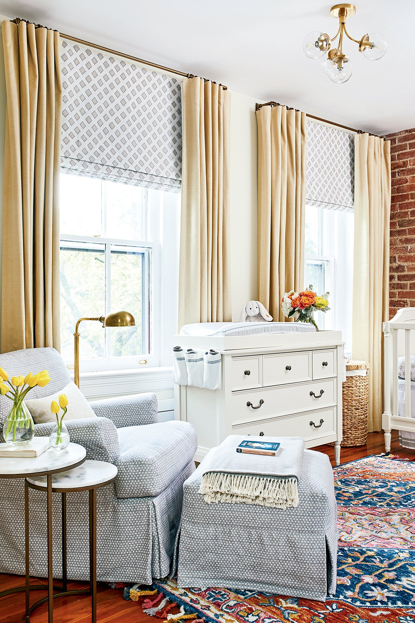 The old master bathroom became this soothing nursery, done up in tans and grays, with a jolt of color from the area rug by Zola. Photograph by Stacy Zarin Goldberg.