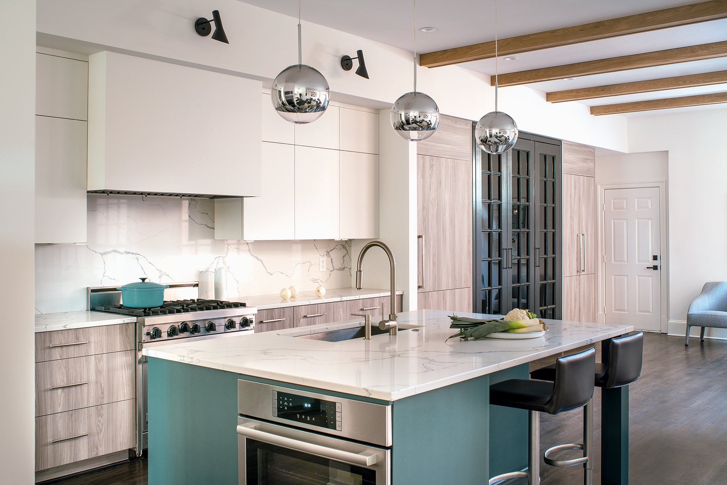 With the different light fixtures and cabinet colors, designer Sarah Kahn Turner unified the space via a single material for countertops and backsplash. Photograph by John Cole Photo.