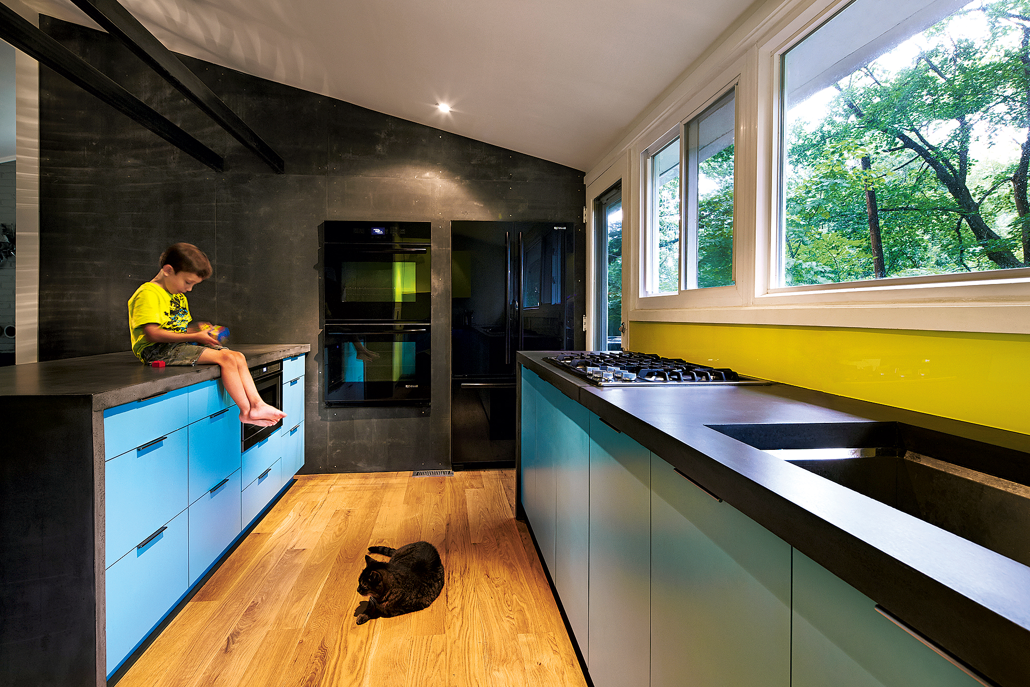 Black concrete counters and a wall clad in Viroc—a matte cement-board paneling—help tone down the bright shades in architect Janet Bloomberg's own kitchen. Photographs courtesy of Kube Architects.
