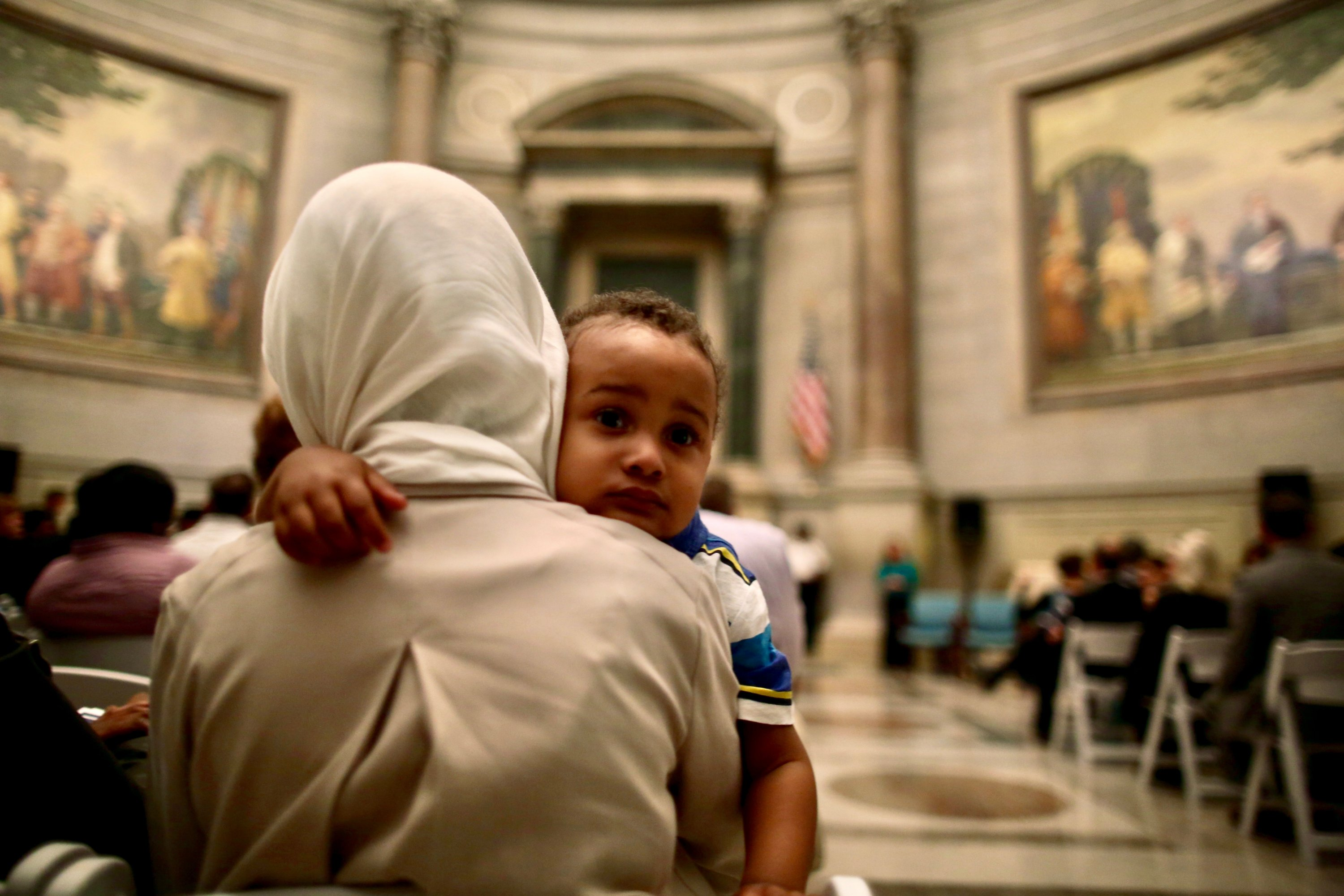 Photographs of Immigrants Becoming U.S. Citizens: A mother holds her child while attending a naturalization service at the National Archives.