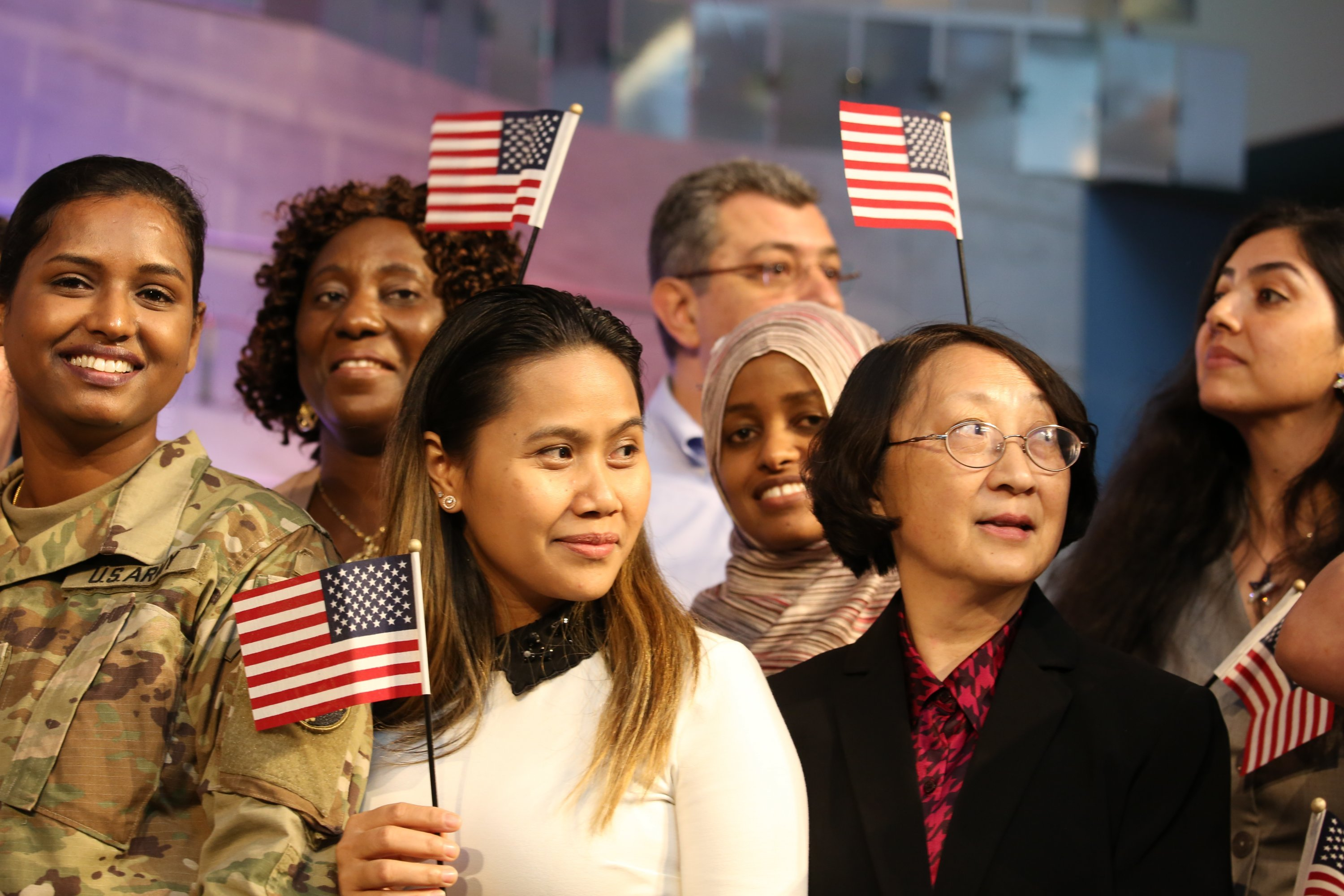 Photographs of Immigrants Becoming U.S. Citizens: Newly minted U.S. citizens wave their flags during a naturalization service at the American History Museum.
