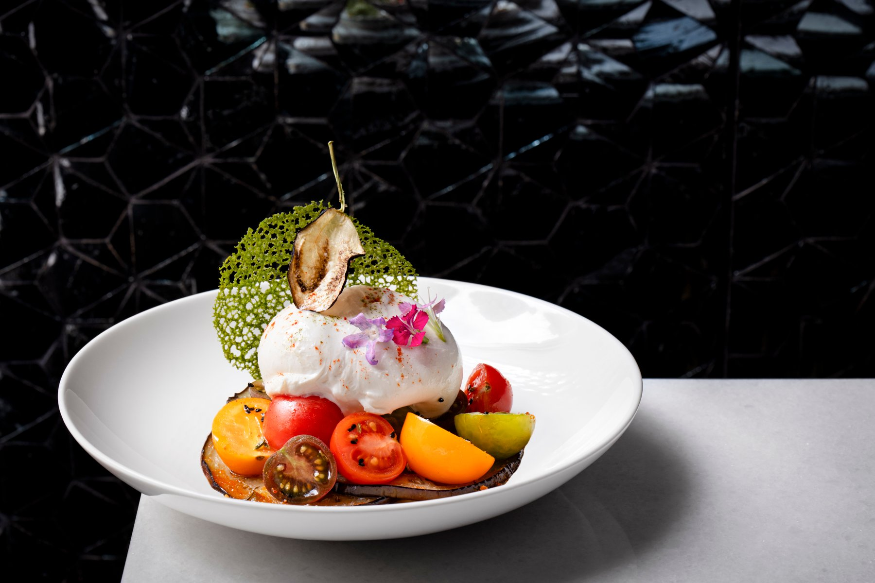 Eggplant, heirloom tomatoes, and burrata pay tribute to Punjabi dairy farmers in Italy. Photograph courtesy of Punjab Grill.