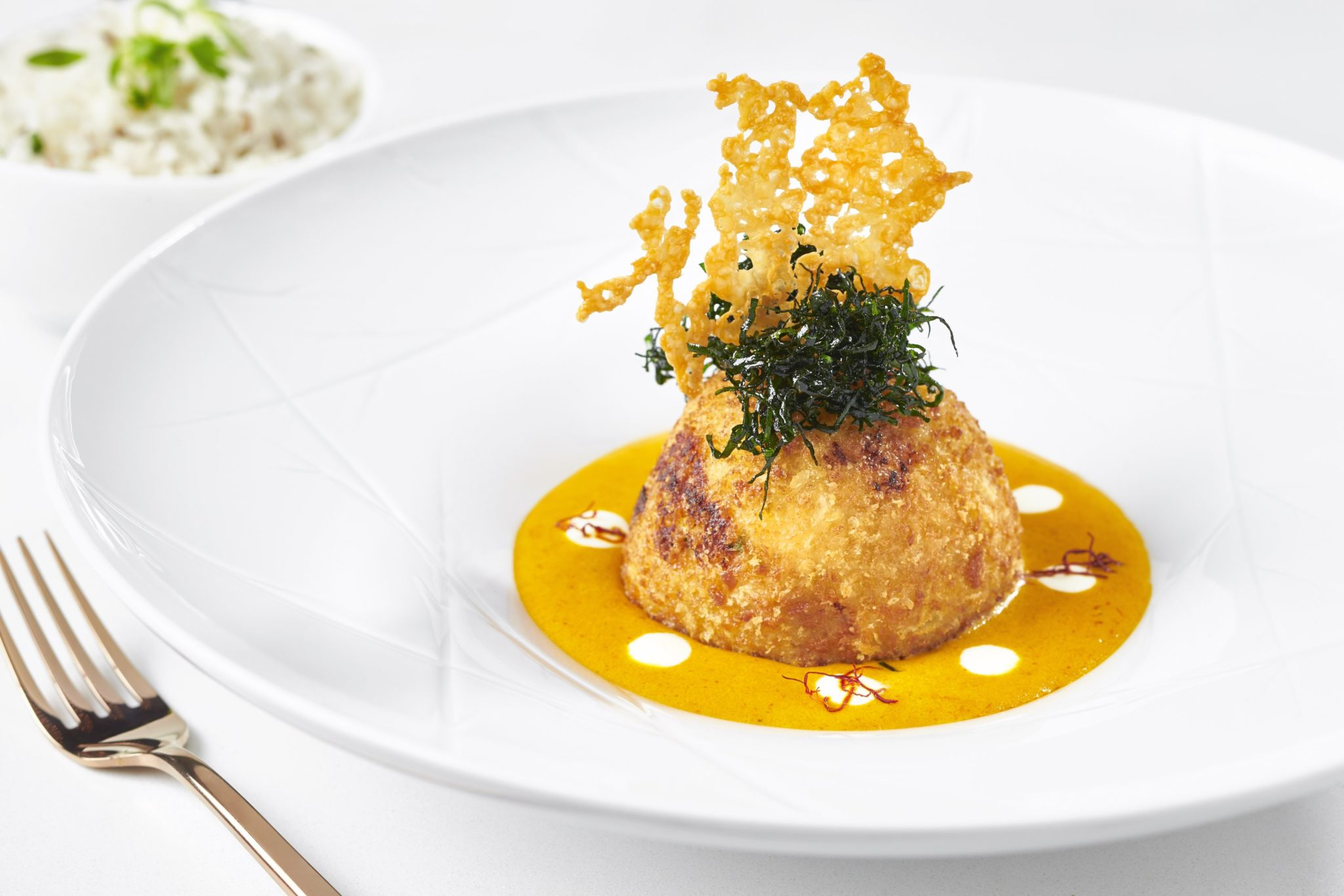 Chef and owner Rajiv Chopra garnishes paneer and 4 cheese kofta with a parmesan wafer. Photograph by Greg Powers.
