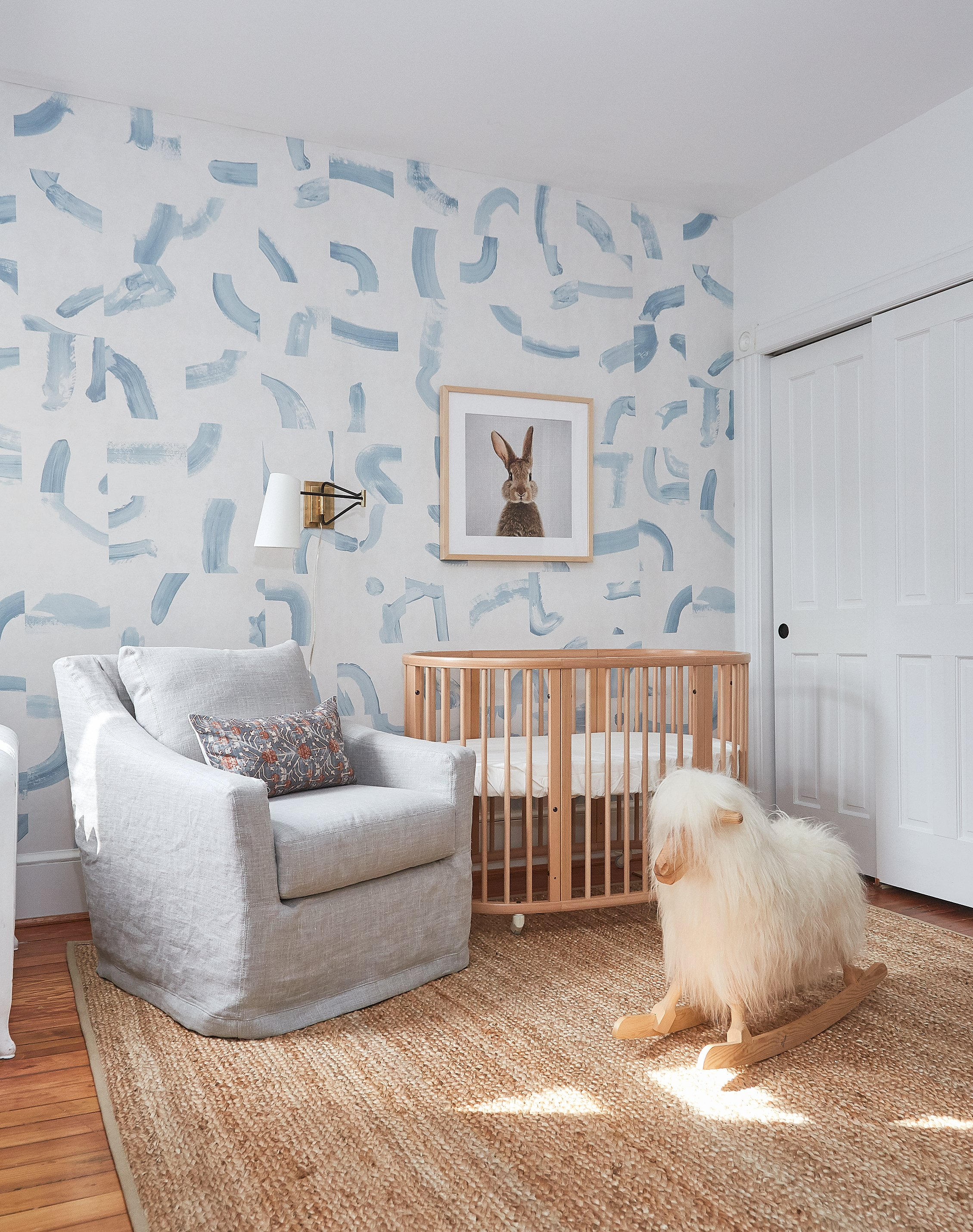 "The baby's room features ""Sepiessa"" wallpaper in sky blue, by Caroline Z Hurley for Schumacher. The modern crib is by Stokke."