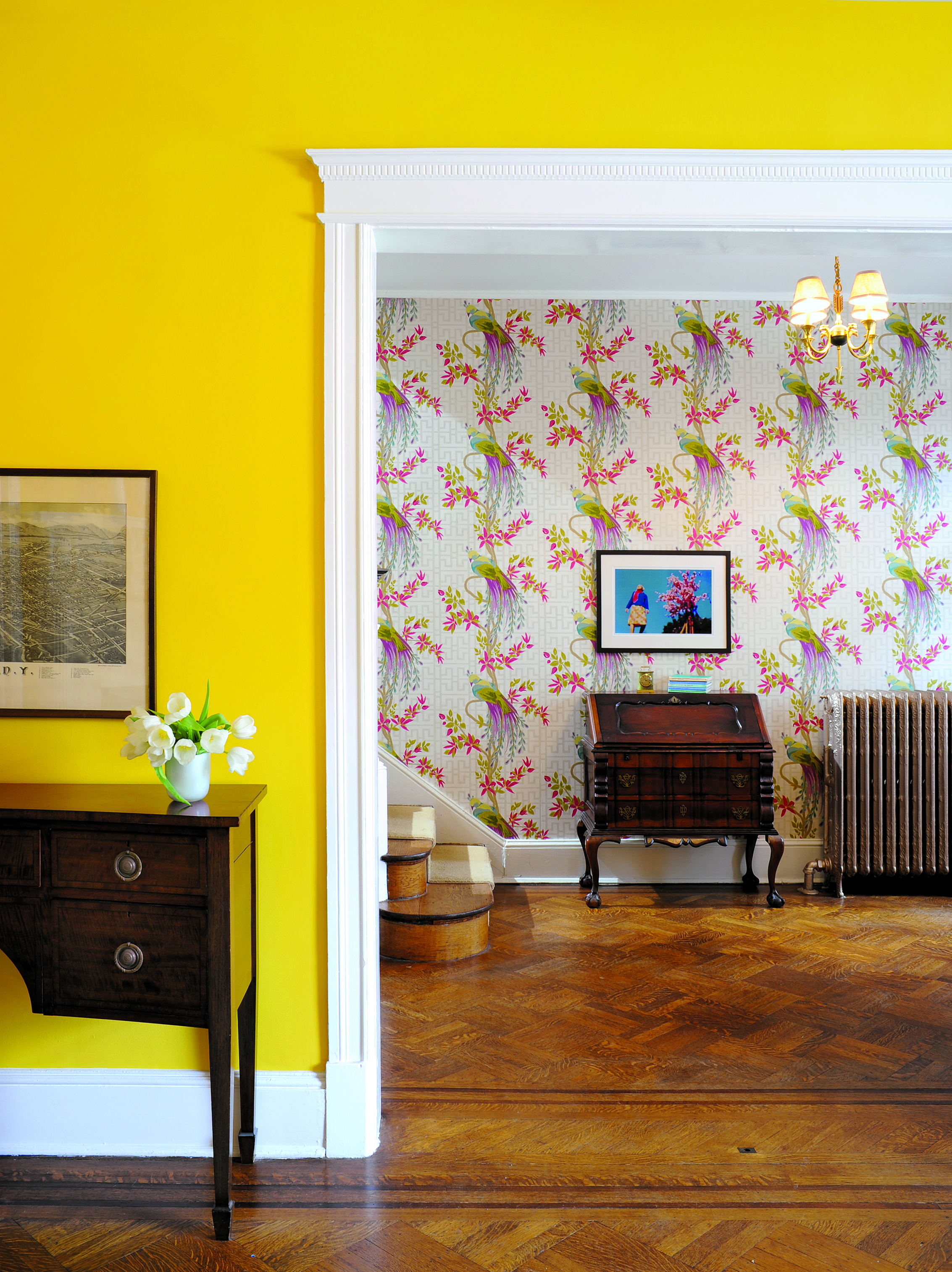 "Off the Wall: Sunny yellow paint and Nina Campbell's ""Paradiso"" wallpaper enliven the foyer. Photograph by Michael Wilkinson."