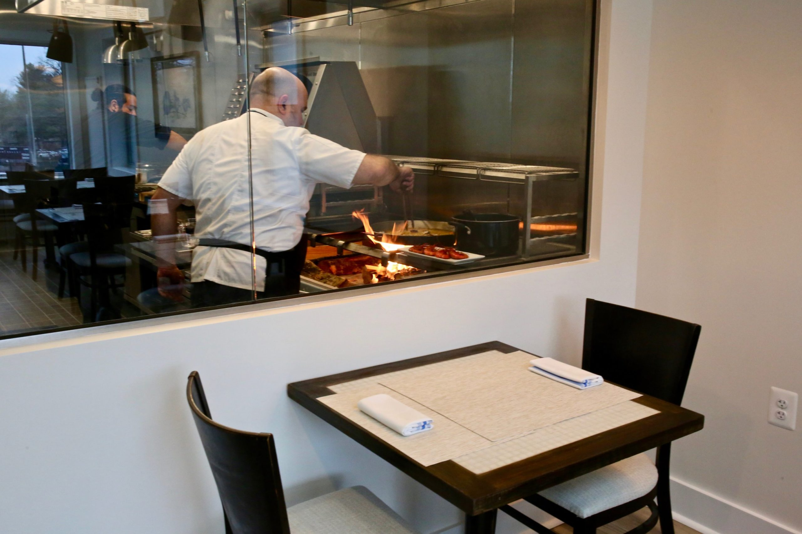 Chef Danny Lledó cooks paella in the glass-enclosed kitchen. Photo by Evy Mages.
