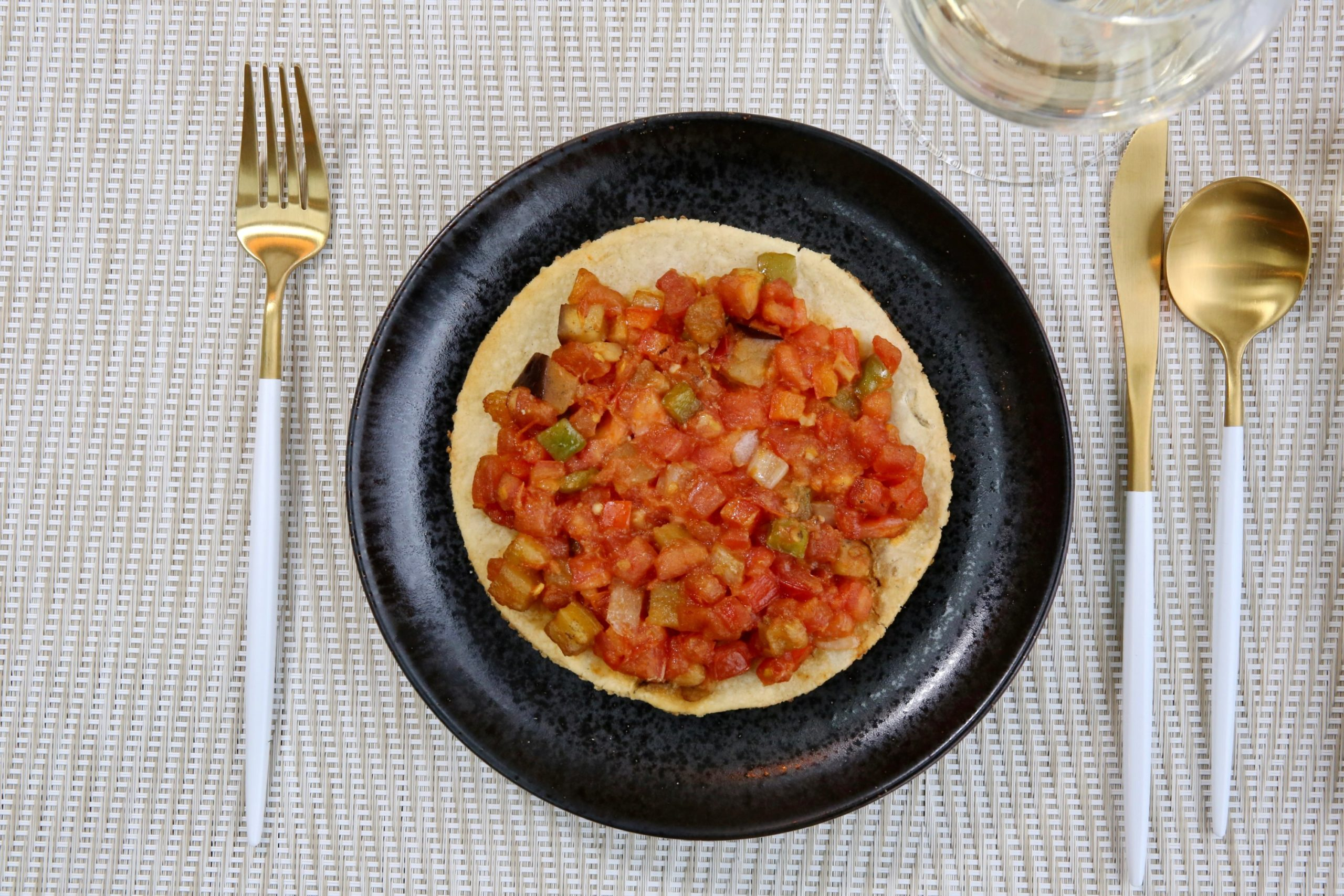 A tomato-topped flatbread is crisped in the green egg over orange wood. Photo by Evy Mages.