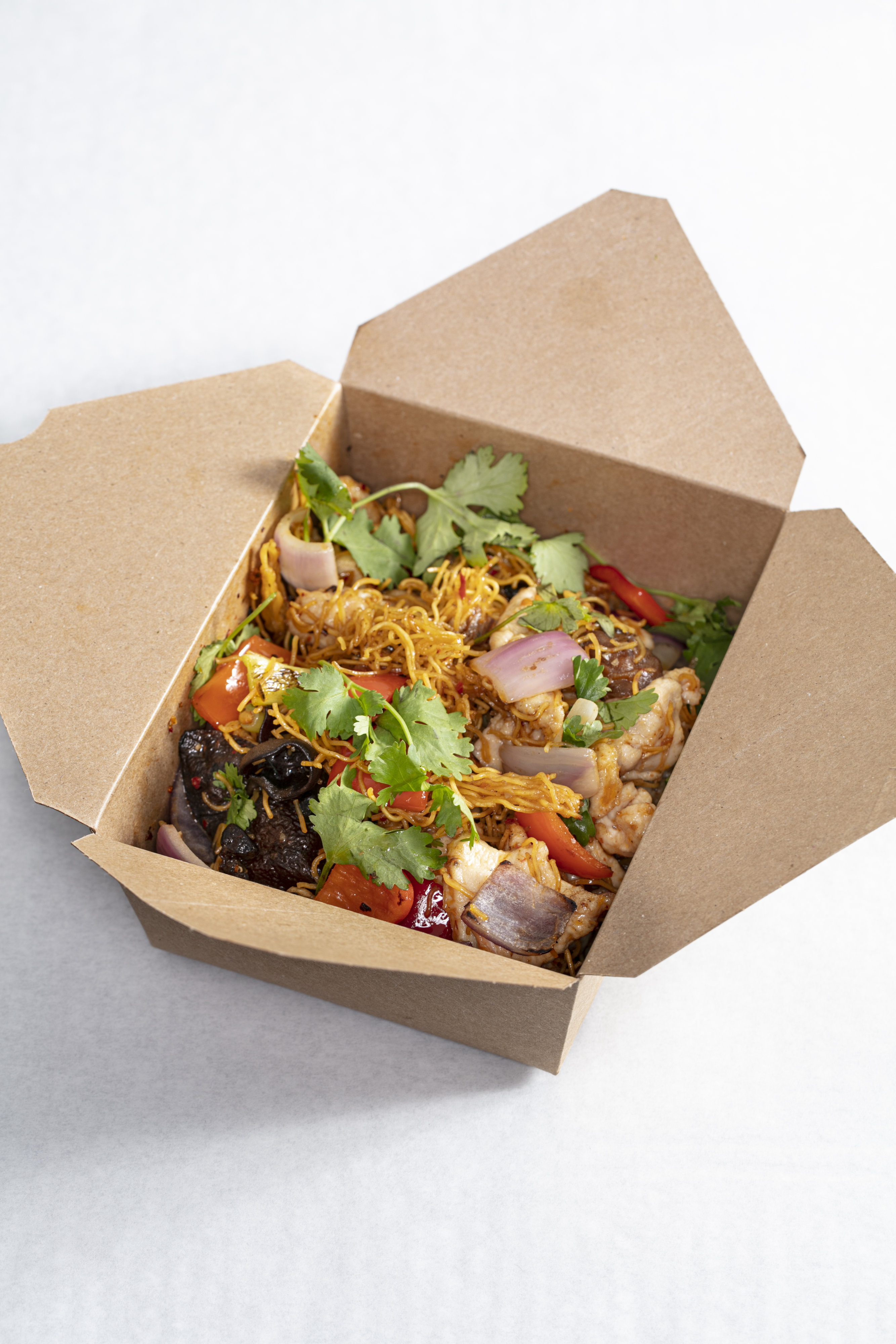 Sustainable packaging, like the recyclable containers for the chili chicken chow mein, is a priority for the team. Photo by Melissa Hom.