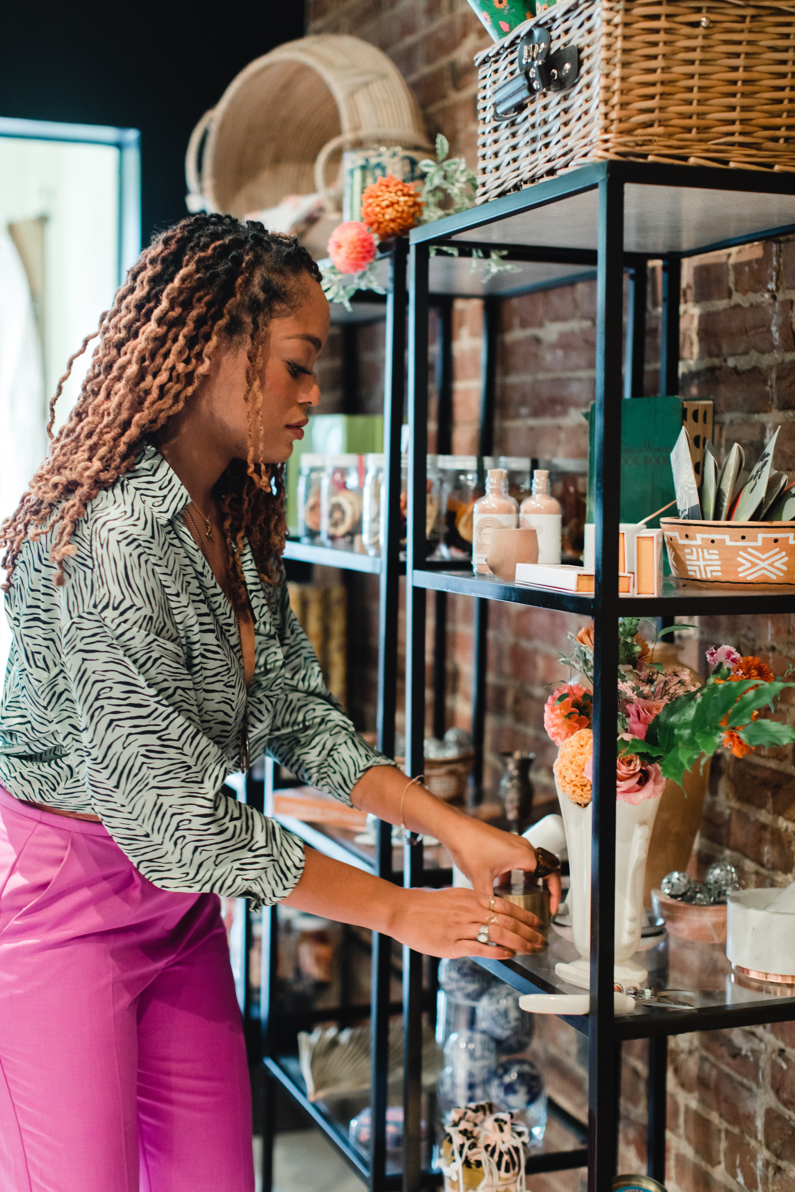 Team member Blaire Bradford adjusts a shelf stocked with curated goods. Photo by Maddie Kaye Photo.